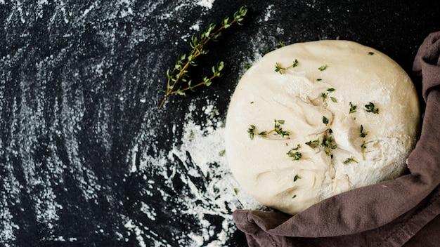Thym sur pâte crue pétrie sur un plan de travail de cuisine noir