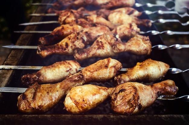 Tibia de dinde grillé pendant la cuisson. poulet rôti à la broche à l'extérieur. vue rapprochée.