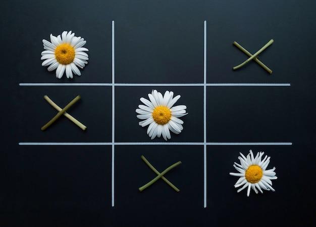 Tic tac toe sur fond noir composé de fleurs de camomille et de brindilles de fleurs. mise à plat. notion naturelle.