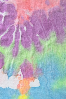 Tie dye pastel, un motif fait main sur un t-shirt en coton. gros plan, vue de dessus. concept de bricolage, artisanat, vêtements de tous les jours originaux, techniques de teinture des tissus. mise à plat, verticale. abstrait .