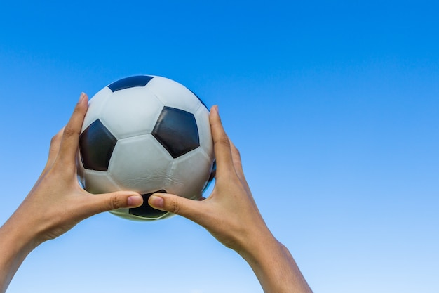Tient un ballon de football dans le ciel sur fond de ciel bleu.