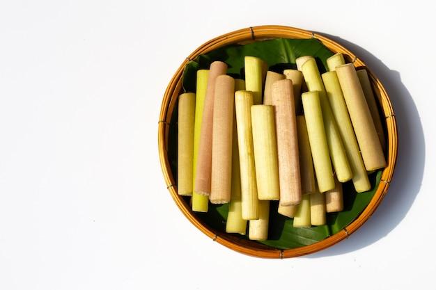 Tiges de lotus pour la cuisson dans un panier en bambou sur une surface blanche
