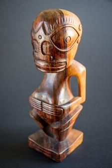 Tiki polynésien traditionnel en bois des îles marquises. isolé sur un fond sombre