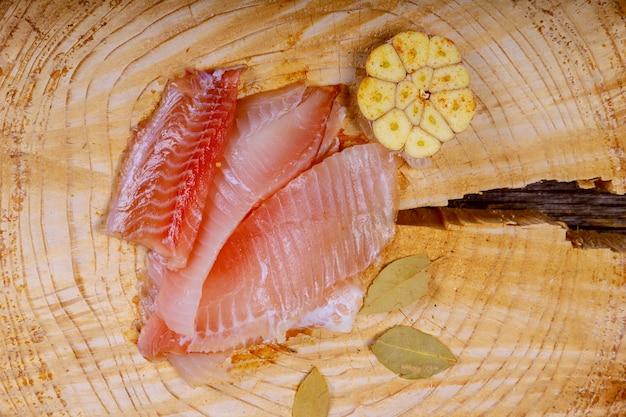 Tilapia frais avec la feuille de laurier et l'oignon sur une planche à découper.
