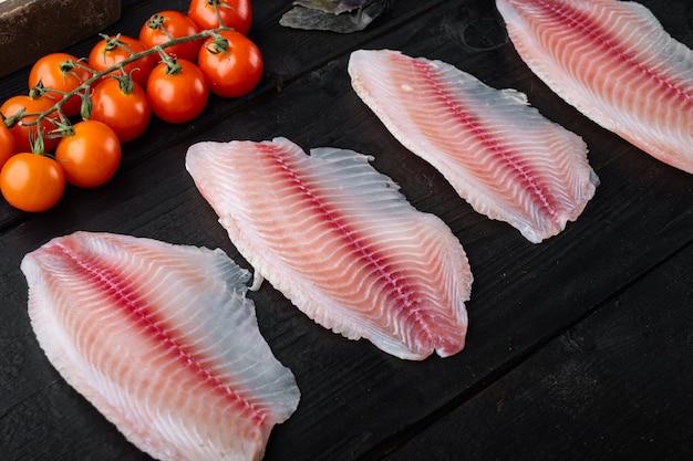 Tilapia de poisson blanc cru, avec du riz basmati et des ingrédients de tomates cerises, sur fond de bois noir
