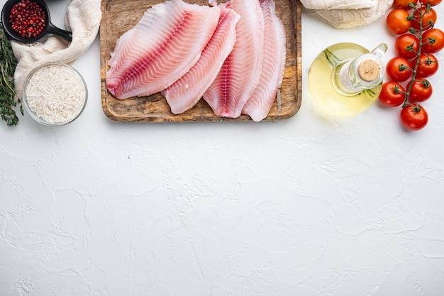 Tilapia De Poisson Blanc Cru, Avec Du Riz Basmati Et Des Ingrédients De Tomates Cerises, Sur Table Blanche, Vue Du Dessus Photo Premium