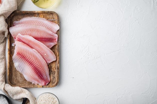 Tilapia de poisson blanc cru, avec du riz basmati et des ingrédients de tomates cerises, sur table blanche, vue du dessus