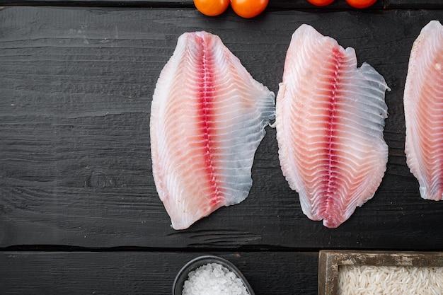 Tilapia de poisson blanc cru, avec du riz basmati et des ingrédients de tomates cerises, sur une table en bois noir, vue de dessus avec copie espace pour le texte