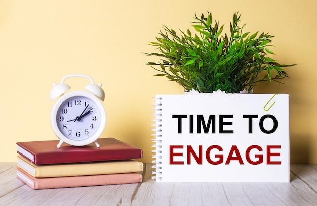 Time to engage est écrit dans un cahier à côté d'une plante verte et d'un réveil blanc, qui se dresse sur des agendas colorés