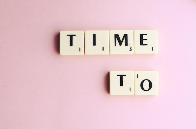 Time to word sur des cubes en bois sur fond rose