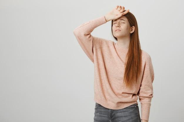 Timide femme rousse mignonne pose comme la reine du drame, tient la main sur le front et soupire