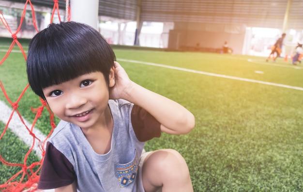 Timide garçon est assis à côté du but de football dans le champ de pratique