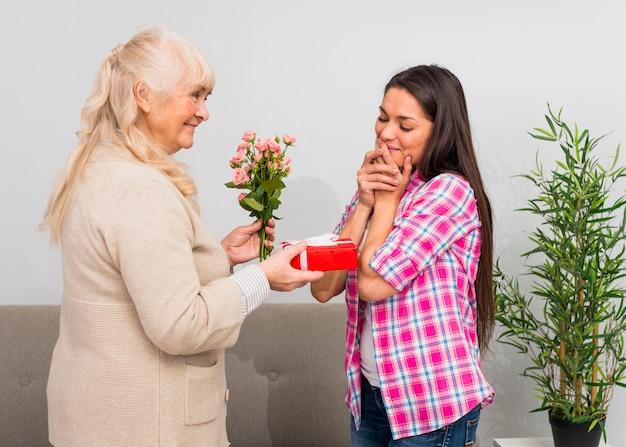 Timide jeune femme regardant souriante mère tenant une boîte cadeau et bouquet de roses