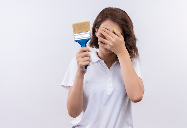 Timide jeune fille aux cheveux courts portant un polo blanc tenant un pinceau couvrant les yeux avec la main
