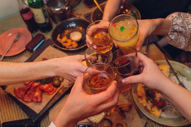 Tintement des verres avec de l'alcool et des toasts, fête.