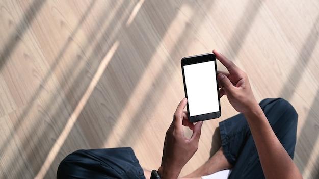 Tir aérien de mains d'homme tenant un téléphone portable avec un écran blanc vierge alors qu'il était assis sur un plancher en bois.