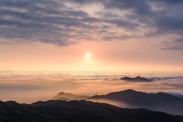 Tir aérien des montagnes sous un ciel nuageux au coucher du soleil