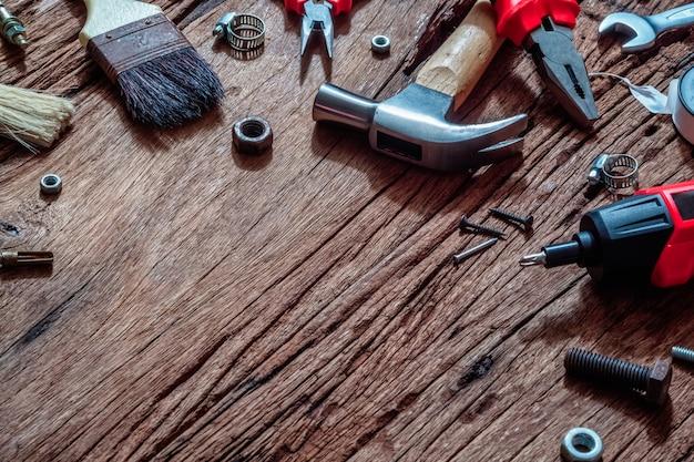 Tir aérien d'outils de construction pratiques variés sur du bois rouillé grunge.