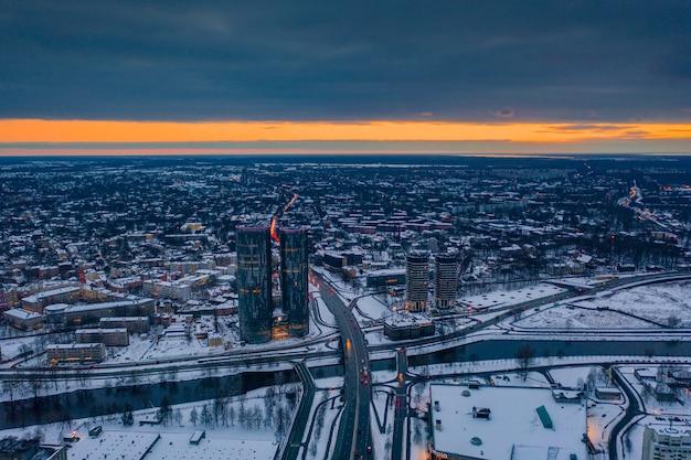 Tir aérien de riga enneigé, lettonie pendant le coucher du soleil orange