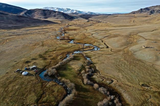 Tir aérien d'une rivière dans une grande prairie sèche