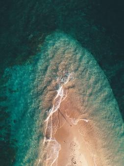 Tir aérien des vagues de l'océan frappant la petite île de sable