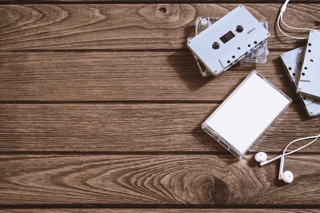 Tir aérien de la vieille cassette audio rétro avec écouteur sur fond en bois rétro vintage, vue de dessus plat lay avec espace copie.