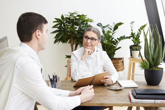 Tir candide d'une femme pdg positive attrayante d'âge moyen dans des lunettes, prendre des notes dans un cahier, écouter de talentueux jeune candidat à un emploi masculin lors d'un entretien dans son bureau confortable