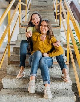 Tir complet des amis heureux assis sur les escaliers