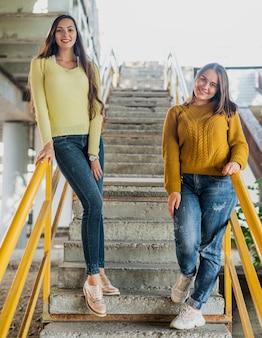 Tir complet des amis heureux dans les escaliers