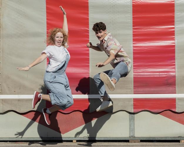 Tir complet couple drôle sauter ensemble