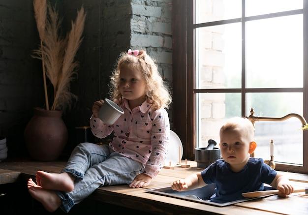 Tir complet enfants assis dans la cuisine