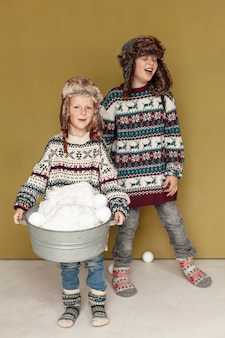 Tir complet enfants heureux jouant avec des boules de neige à l'intérieur