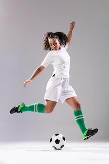 Tir complet femme adulte jouant au football