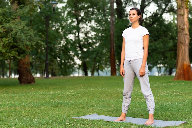 Tir complet femme debout sur un tapis de yoga