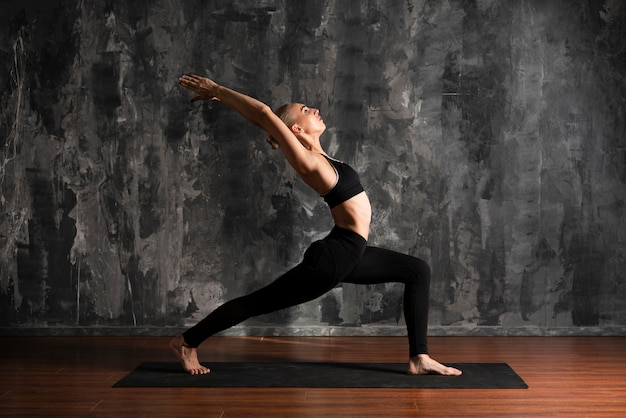 Tir complet femme faisant du yoga sur tapis