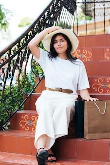 Tir complet femme tenant son chapeau