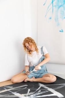 Tir complet femme versant de la peinture blanche sur un pinceau