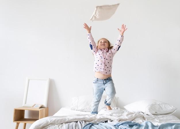 Tir complet fille jouant avec un oreiller