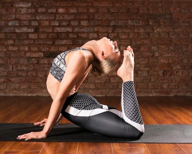 Tir complet position complexe femme sur tapis noir