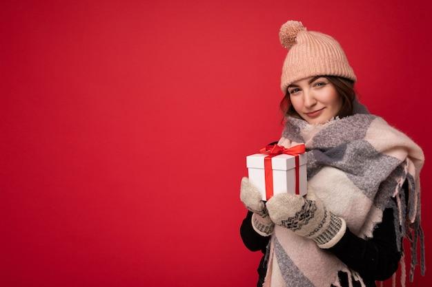 Tir confortable de charmante heureuse jeune femme brune mignonne isolée sur fond rouge