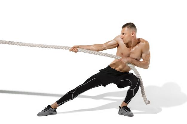 Tir à la corde jeune athlète masculin élégant pratiquant sur le mur blanc du studio