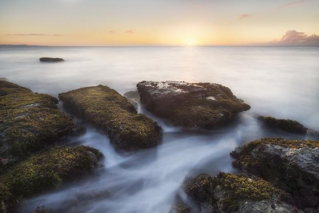 Tir à couper le souffle d'énormes pierres dans l'océan avec l'eau mousseuse qui les traverse