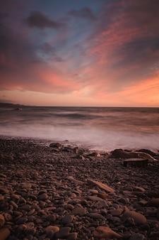 Tir à couper le souffle d'une plage rocheuse sur un fond de coucher de soleil