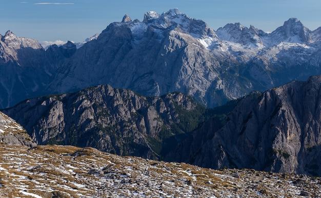 Tir à couper le souffle de roches enneigées dans les alpes italiennes sous le ciel lumineux