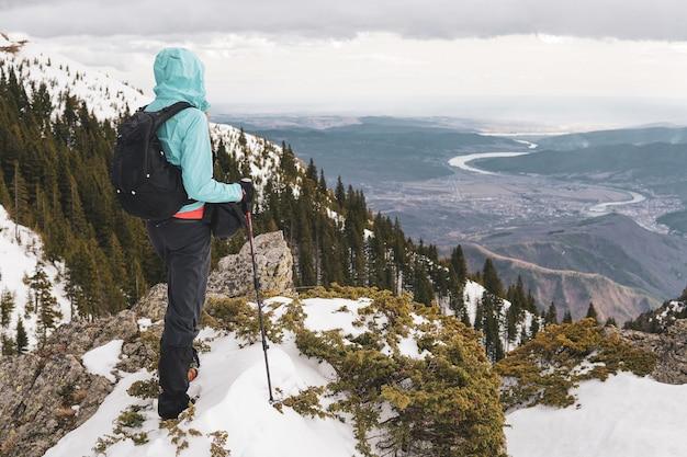 Tir derrière un homme debout au sommet d'une montagne des carpates avec vue sur la rivière olt en roumanie