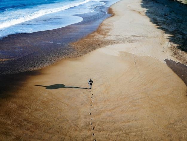 Tir de drone de surfeur marchant sur le rivage