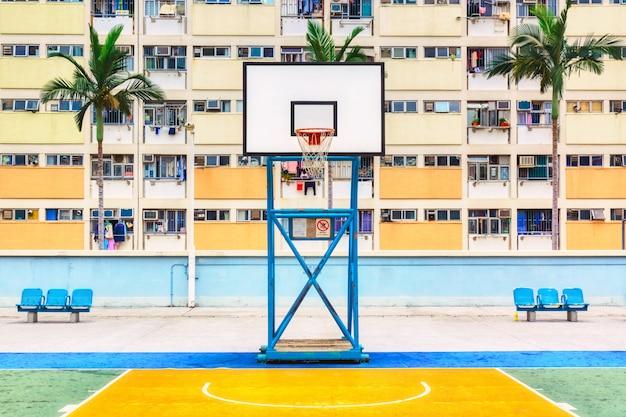 Tir emblématique du terrain de basket de hong kong avec des palmiers et un immeuble coloré