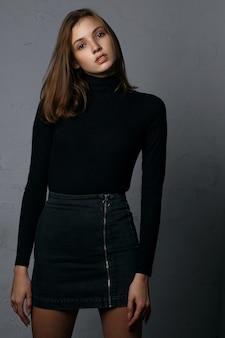 Tir d'essai pour une jolie jeune mannequin portant une jupe en jean et un pull noir