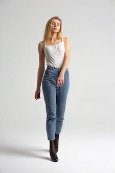 Tir d'essai sur toute la longueur pour un jeune mannequin à la mode posant sur fond blanc