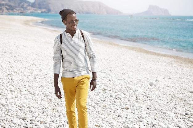 Tir d'été en plein air de jeune touriste afro-américain en chapeau et lunettes de soleil élégantes, portant un sac à dos sur ses épaules, marchant le long de la plage de galets, l'air heureux et insouciant, profitant du paysage marin